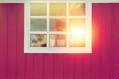 Windmill reflection in window on red wood background. Windmill reflection in window on red wood background of farmhouse in sunset Royalty Free Stock Images