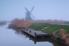 Windmill by river in dense fog Stock Photo