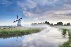 Windmill and river in foggy morning Royalty Free Stock Image