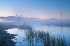 Windmill by river in misty dusk Stock Photo