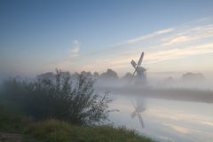 Windmill by river in morning fog Stock Photography