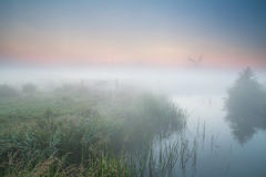 Windmill and river in morning fog Stock Image