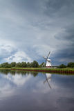 Windmill by river over clouded stormy sky Royalty Free Stock Photo