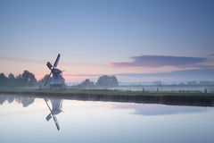 Windmill by river at sunrise Royalty Free Stock Photography
