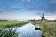 Windmill by river at sunset Royalty Free Stock Photo