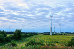 Windmill on rural field in the sunset. Wind turbines farm. Royalty Free Stock Image