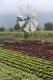 A Windmill and salad crop being irrigated. Windmill and mountains on the Lasithi plateau Crete, Greece. October 2017. Windmills pump water to this Cretan fertile Royalty Free Stock Photos