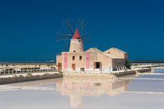 Windmill and salt pans at the salina of Trapani. The salt museum with a traditional windmill with a red roof and reflection in the salt pans at the salina of Royalty Free Stock Image
