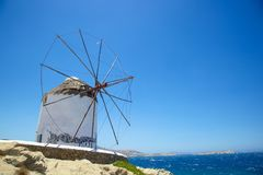 Windmill beside the sea at Mykonos. Whitewashed windmill with thatched conical  roof on the Greek island of Mykonos  beside the sea, blue sky Royalty Free Stock Photography