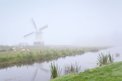 Windmill and sheep by river in fog Stock Photo