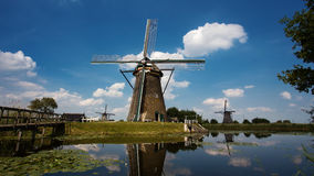Windmill on the shore of the lake. A windmill located on the shore of the lake, shot in the afternoon Stock Photography