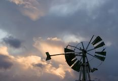 Windmill Silhouette. Broken down windmill silhouetted against the setting sun royalty free stock image
