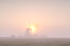 Windmill silhouette in dense fog at sunrise Royalty Free Stock Images
