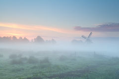 Windmill silhouette in dense morning fog Stock Images
