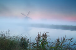 Windmill silhouette in dense sunrise fog Royalty Free Stock Image
