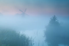 Windmill silhouette in dense sunrise fog Stock Image