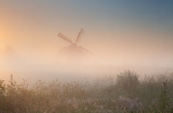 Windmill silhouette in sunrise fog Stock Images