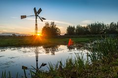 Windmill Silhouetted Against the Setting Sun royalty free stock photos