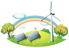 A windmill and solar energy panels Stock Photos