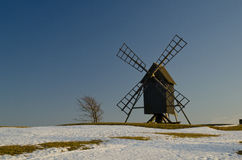 Windmill in springtime. Early springtime with melting snow and a windmill in evening sun Royalty Free Stock Photography