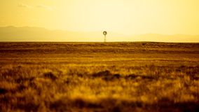 Windmill standing in the distance. A windmill stands proud in the distance as the sun sets behind the distant mountains Royalty Free Stock Photography
