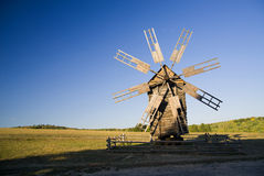 Windmill standing in the field against the blue sky Royalty Free Stock Photos