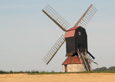 Windmill by stubble field. Stock Image