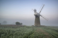 Windmill in stunning landscape on beautiful Summer dawn Royalty Free Stock Photography