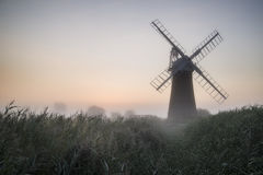Windmill in stunning landscape on beautiful Summer dawn Stock Photos