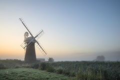 Windmill in stunning landscape on beautiful Summer dawn Royalty Free Stock Image