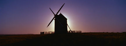 Windmill sunset. Windmill with sun setting behind close to Mont San Michel France.Copyspace royalty free stock photography