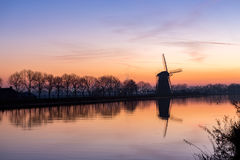 Windmill at sundown in Nieuwe Wetering. Sundown at windmill `the Googermolen` with reflection in the water on the Ringvaart canal in Nieuwe Wetering the royalty free stock photo