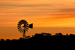 Windmill at Sunrise. Dramatic sunrise with a windmill in Arizona Stock Photo