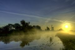 Windmill, sunrise and mist stock photography