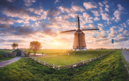 Windmill at sunrise in Netherlands. Spring panoramic landscape. Windmill at sunrise in Netherlands. Traditional dutch windmill, green grass, fence  against Royalty Free Stock Photo