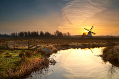 Windmill during sunrise reflected in river Stock Images