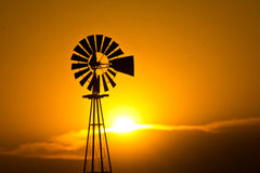 Windmill at Sunset. Silhouette of a windmill in front of a hot Kansas summer sunset Royalty Free Stock Image