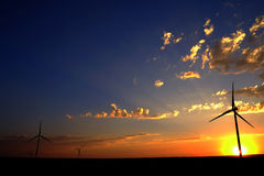 Windmill at Sunset Generating Sustainable Power. Windmill with sunset and clouds generating electricity and sustainable power royalty free stock photos
