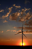 Windmill at Sunset Generating Sustainable Power. Windmill with sunset and clouds generating electricity and sustainable power royalty free stock image