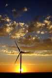Windmill at Sunset Generating Sustainable Power. Windmill with sunset and clouds generating electricity and sustainable power stock photo
