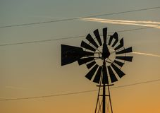 Windmill at sunset. Livestock windmill and converging lines at sunset Stock Images