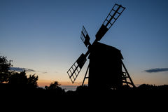 A windmill at sunset. An old windmill at sunset royalty free stock photography