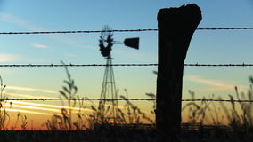 Windmill Sunset. Rack focus from some grass and a barbed wire fence in the foreground to a old fashioned windmill in the background during sunset stock footage