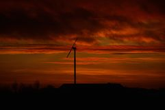 Windmill in sunset. Windmill is surrounded by lava-colored clouds of the sunset Stock Images