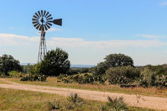 Windmill in the Texas Hill Country. Windmill and prickly pear cactus on a dirt road in the Texas Hill Country Royalty Free Stock Image