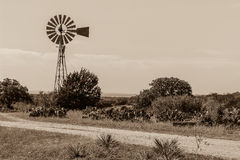 Windmill in the Texas Hill Country. Sepia tone of a windmill and prickly pear cactus on a dirt road Stock Image