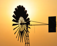 Windmill. To draw water from a well with sun background Stock Images