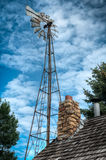 Windmill Towers Over Building. With cloudy sky royalty free stock photography