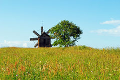 Windmill and tree in the field Stock Images
