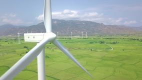 Windmill turbine on blue sky and mountain landscape. Wind power generator for clean renewable energy aerial view. Drone. View wind farm in green field stock footage